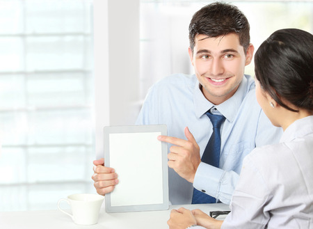 Image of two young business partners using touchpad at meeting photo