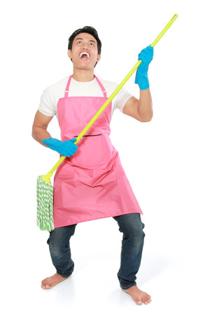 air guitar: Cleaning man happy excited during cleaning. Funny man with cleaning mop playing guitar isolated on white background