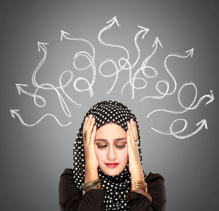 undetermined: Closeup portrait of young muslim woman stressed having so many thoughts