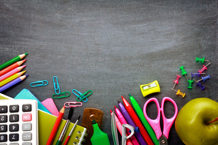 education: School supplies on blackboard background ready for your design