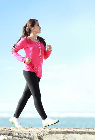 Szczęśliwa zdrowa dziewczyna robi szybki marsz na plaży