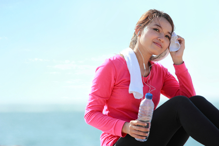Portrait of asian healthy fitness woman holding a bottle of water while having a break photo