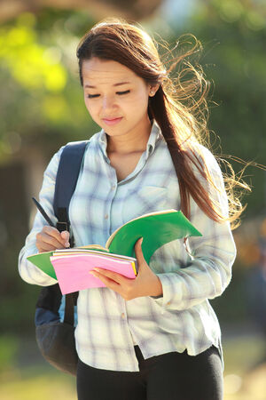 Girl writing something on the books in campus park photo