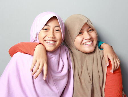 portrait of two young muslim girl best friend having smiling together on grey background photo