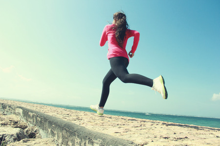 Beautiful healthy girl in pink running on the beach photo