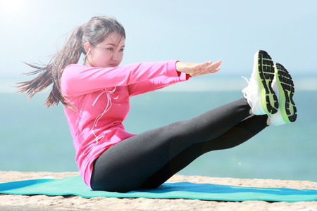 sporty asian woman warming up stretch her legs in the beach photo