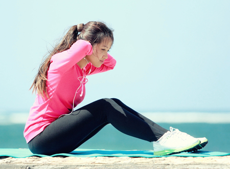 sit up: sporty asian woman sit up stretch her legs in the beach Stock Photo