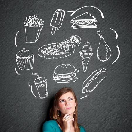 eten: portret van verwarren jonge vrouw op zoek te denken wat te eten. fast food concept
