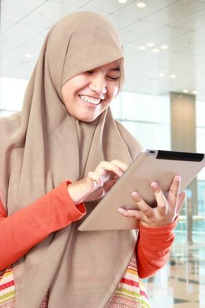 happy muslim kid in head scraf using tablet computer photo