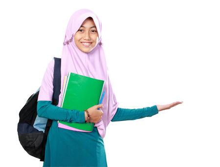 Portrait of happy muslim kid student holding books presenting something on white background photo
