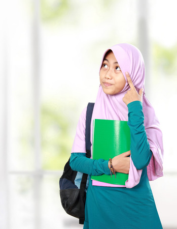 何かを考えて本を保持している肖像画のイスラム教徒の子供学生