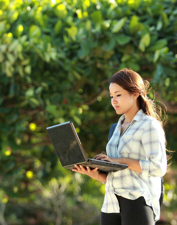 Young student doing homework with laptop in the park photo