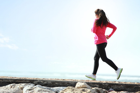 jogging track: Happy healthy girl running on the beach