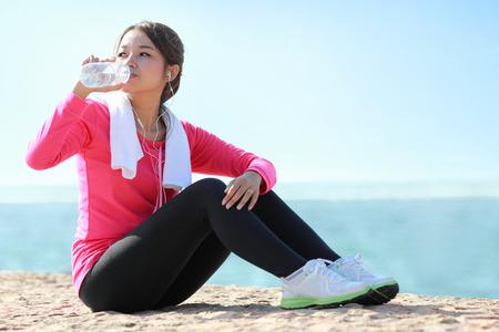 Portrait der asiatischen sportliche Fitness Frau trinkt eine Flasche Wasser, während eine Pause Standard-Bild