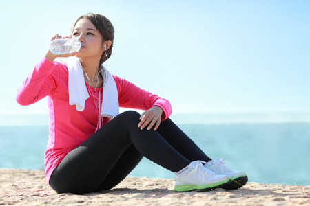 Portrait of asian sporty fitness woman drinking a bottle of water while having a break Stock Photo