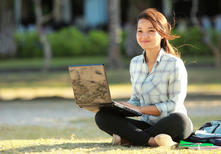 Young student sitting cross-legged on grass with laptop doing a homework photo