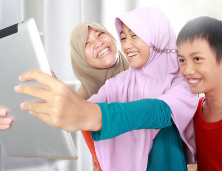 portrait of happy three muslim kids taking picture with tablet computer in school Stock Photo