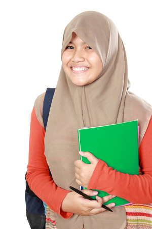 Portrait of happy muslim kid student holding books photo