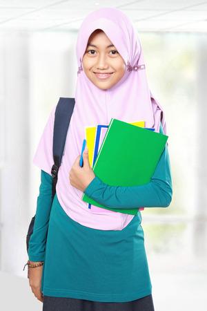 Portrait of happy muslim kid student holding books photo