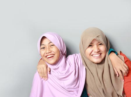 Portrait de deux jeunes attrayant musulman enfant de s'amuser ensemble sur fond gris Banque d'images - 30856944