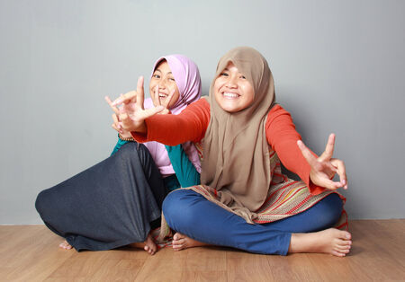 portrait of attractive two young muslim kid having fun together on grey background photo