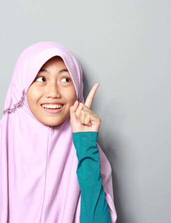 Portrait of attractive young muslim girl pointing up on grey background photo