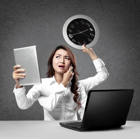 trabajando duro: ocupado empresaria multitarea trabajando duro en la mesa
