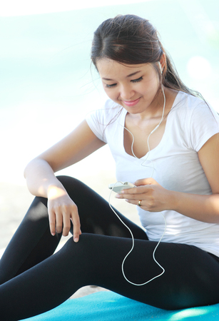 sports wear: Portrait of sporty young woman in sports wear using cellphone