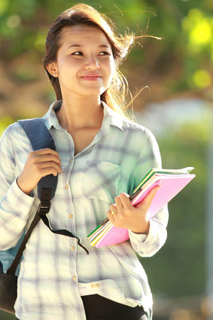 Portrait of beautiful young woman with bag and books walking in campus park photo