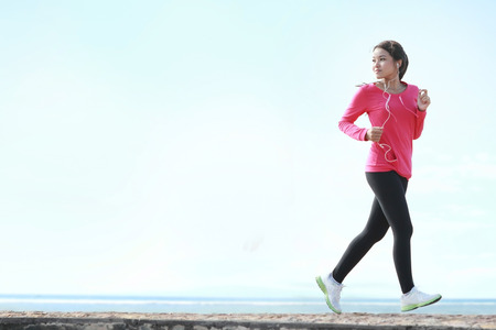 Beautiful healthy woman in pink running on the beach photo