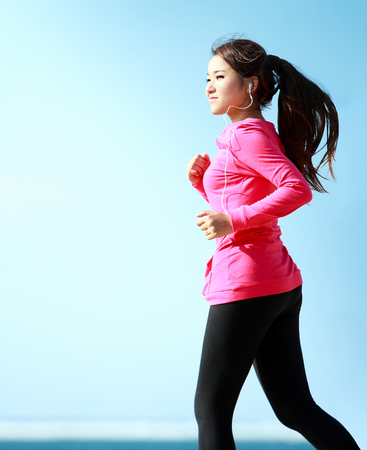Beautiful healthy girl in pink running on the beach