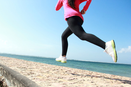 closeup legs of woman running on the beach photo