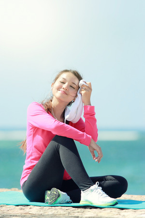 Portrait of beautiful girl having a break on the beach after doing some exercise Stock Photo
