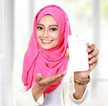 femme musulmane: portrait de jeune femme asiatique montrant l'écran du téléphone portable blanc