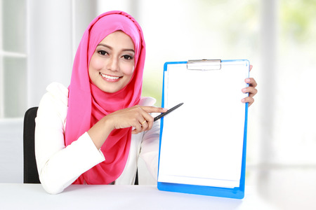 muslim girl: portrait of young asian woman showing blank document