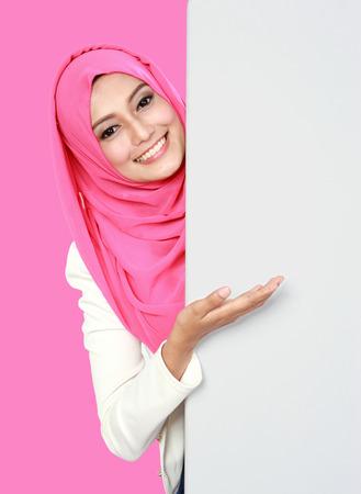 portrait of woman wearing scarf showing blank board Stock Photo