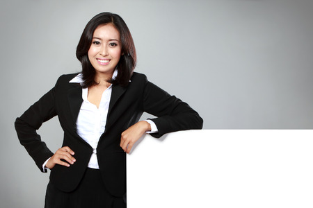 Portrait of a beautiful business woman holding a blank billboard. Ready to add text. photo