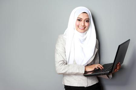 랩톱 컴퓨터를 사용하는 동안 웃는 아시아 여자의 초상화