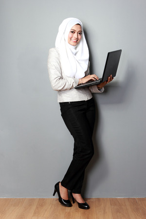 portrait of asian woman smiling while using laptop computer Stock Photo