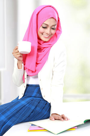 moslem: young girl having a cup of tea while studying