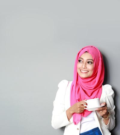 retrato de la joven mujer que piensa que tiene una taza de té