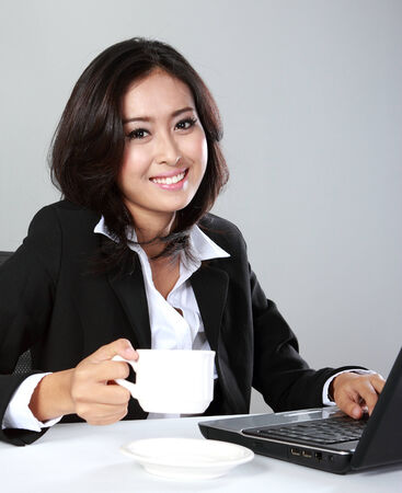 relaxing businesswoman with laptop on grey background photo