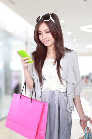 Happy young woman using mobile phone during going shopping in the mall photo