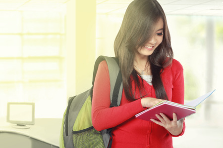 Beautiful female student holding and reading a book