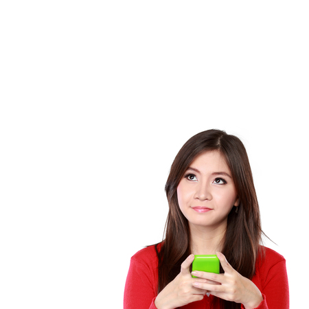 portrait of beautiful girl looking up to blank space and holding mobile phone, ready for your design photo