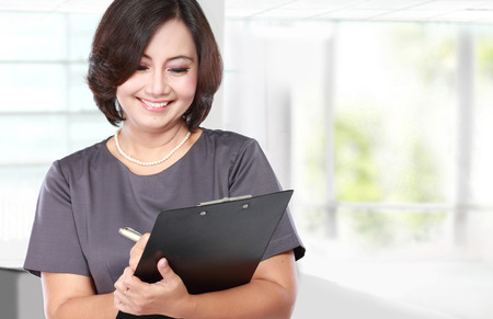 portrait of mature Business woman holding a clipboard Stock Photo