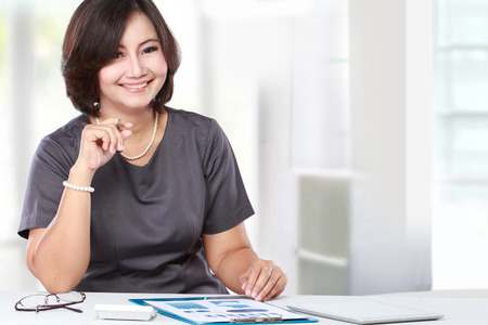 happy asian people: business woman sitting and working in the office