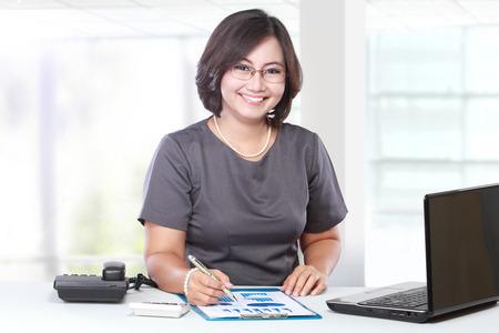 座っているとテーブルの上を書くビジネス女性 写真素材