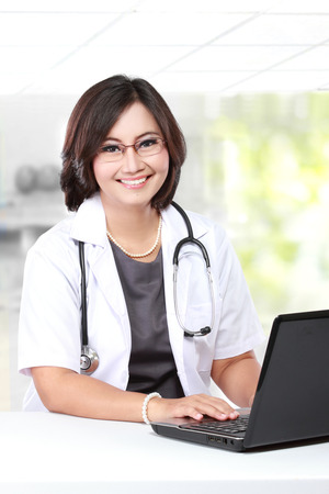 Woman doctor writing a clipboard while using laptop Stock Photo