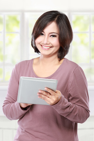 portrait casual middle aged  Woman holding and touch tablet computer photo